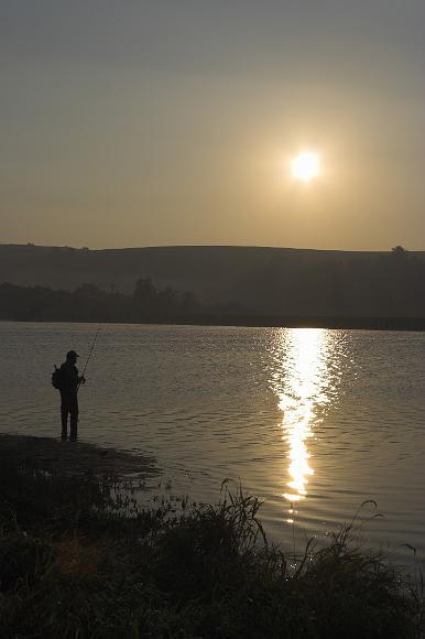 Rybár pri priehrade počas východu slnka